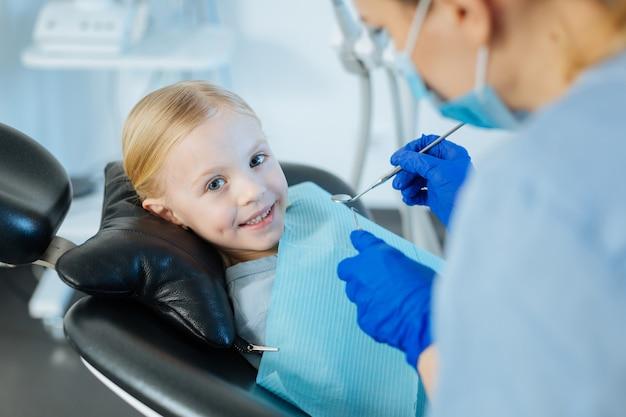 Жизнерадостная маленькая девочка лежит в кресле стоматолога и улыбается во время профессионального лечения зубов у стоматолога-женщины