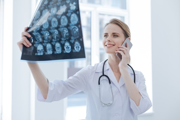 Upbeat lively young radiologist working at the x ray cabinet while examining brain x ray and using smartphone