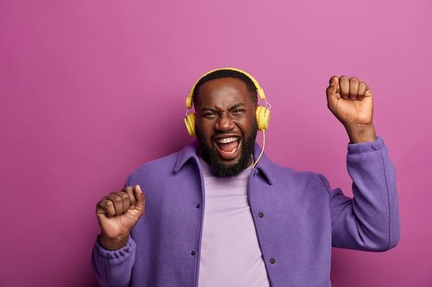경쾌한 남자는 인생을 즐기고, 멋진 음악에 열광하고, 재미 있고, 팔을 들고, 리듬에 맞춰 움직이면서 주먹을 쥐고, 귀에 현대 스테레오 헤드폰을 착용합니다.