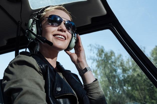Оптимистичное настроение. красивый пилот вертолета весело улыбается, слушая авиадиспетчер в наушниках