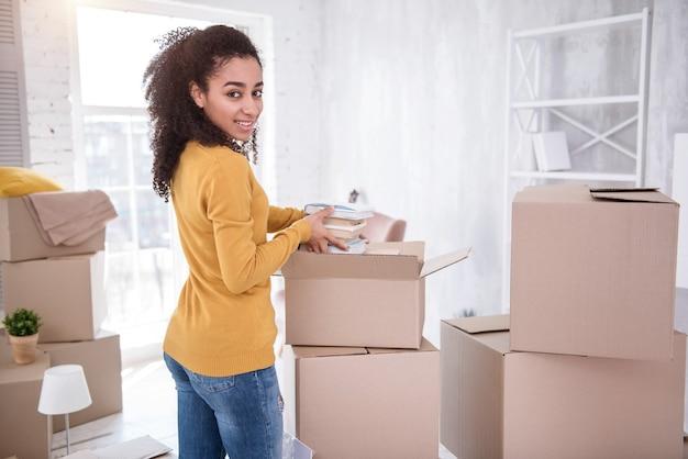 明るい気分。荷物を開梱し、箱から本の山を取り出しながらカメラに微笑んでいる美しい少女