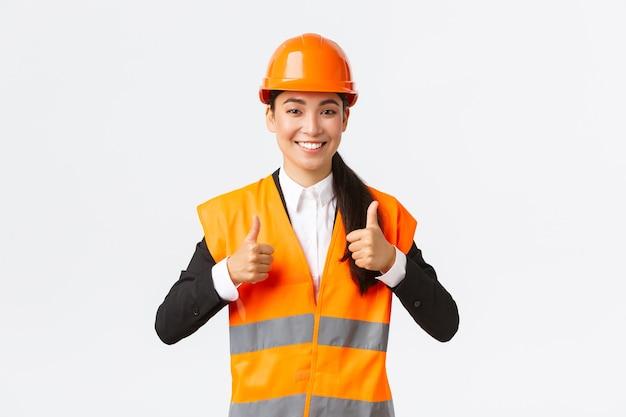 明るいアジアの女性建築家が許可を与え、結果に誇りを持ち、安全ヘルメットと反射ジャケットに立って、承認を得て親指を立て、最高の建設品質を保証します