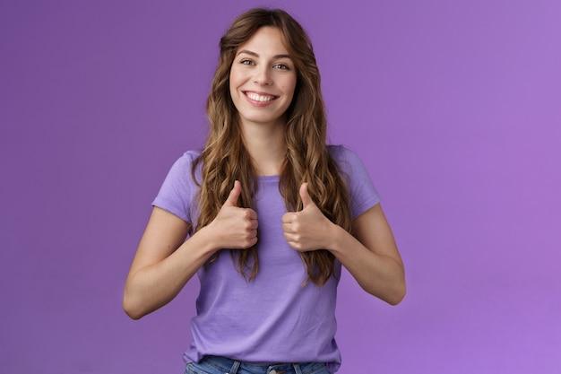 明るいポジティブな魅力的な陽気な巻き毛の女の子は、肯定的な意見の紫色の背景のように満足して立ってよくやった友人の良い仕事を奨励する笑顔を喜んで承認サインを親指を表示します。ライフスタイル。