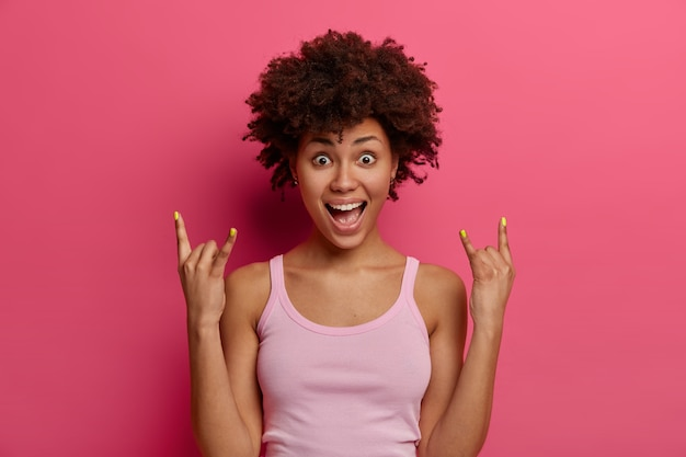 낙관적 인 긍정적 인 민족 여성이 락 앤 롤 염소 제스처를 만들고, 진정한 헌신적 인 로커가되고, 야생 파티에 참석하고, 즐거운 표정을 짓고, 춤을 추며, 재미 있고, 분홍색 벽 위에 고립되어, 미쳤습니다.