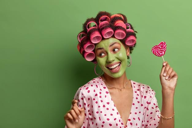 明るい笑顔の女性は、のんびりと踊り、腕を上げて動き、家で楽しんで、美容処置を受け、さわやかな肌にフェイスマスクを適用し、ヘアカーラーを着用し、おいしいロリポップを保持します