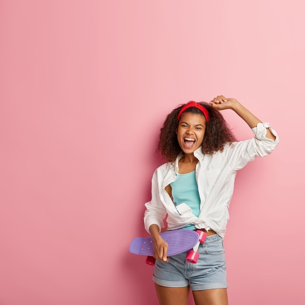 明るい若いアフロアメリカ人女性は手を上げ、満足し、白いシャツとデニムのショートパンツを着て、幸せで叫び、口を開けたままにし、紫色のロングボードを運び、ピンクの壁にモデルを置きます