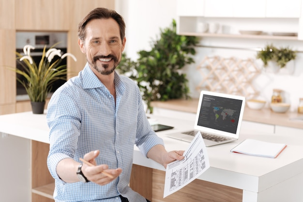 Upbeat young man sitting next to the kitchen counter, holding a printout and reaching out a hand to the camera as if going to address someone