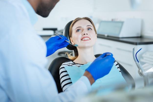 Жизнерадостная молодая женщина сидит в кресле стоматолога и показывает зубы своему стоматологу, пока он держит зеркало для рта и зонд