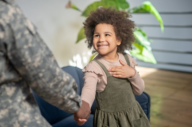 Upbringing. smiling curly cute african american little girl shaking hand daddy in camouflage uniform standing at home