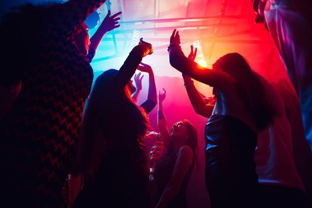 今後。シルエットの人々の群衆は、ネオンの光の背景のダンスフロアに手を上げます。ナイトライフ、クラブ、音楽、ダンス、モーション、若者。パープルピンクの色と感動的な女の子と男の子。