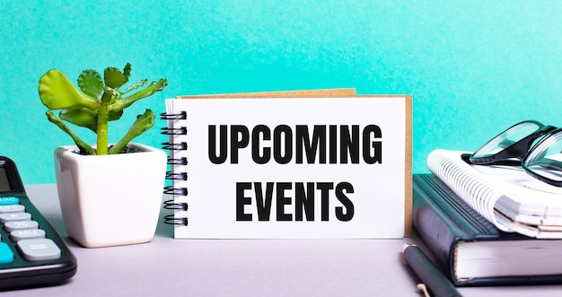 Upcoming events is written on a white card next to a potted flower, diaries and calculator