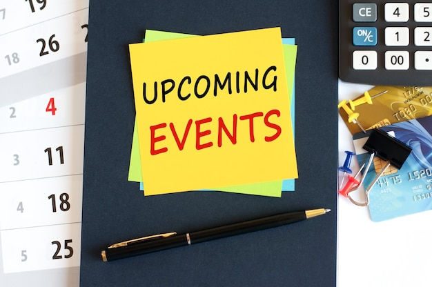 Upcoming events - text on yellow paper on blue background, concept