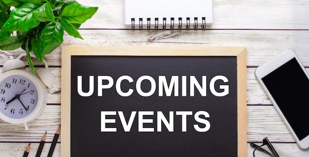 鉛筆、スマートフォン、白いメモ帳、鉢植えの緑の植物の近くの黒い表面に書かれた今後のイベント