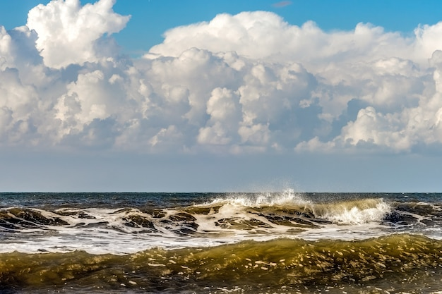 Upcoming storm clouds and breaking waves at kijkduin beach in the hague
