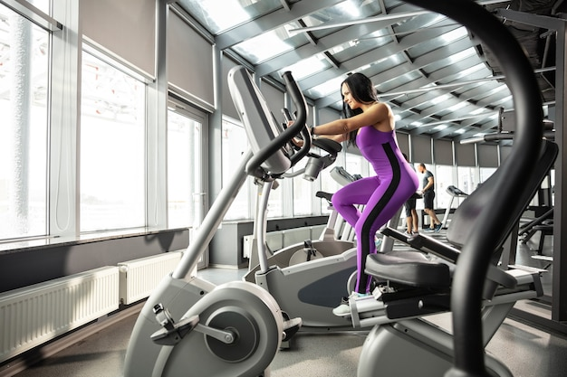 Upcoming. young muscular caucasian woman practicing in gym with cardio. athletic female model doing speed exercises, training her lower, upper body. wellness, healthy lifestyle, bodybuilding.