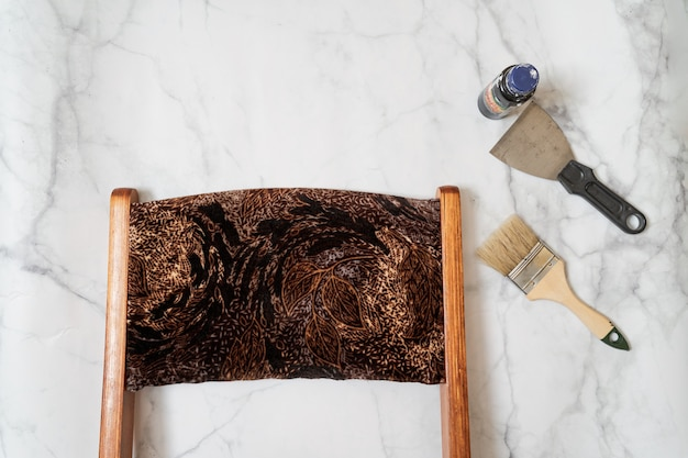 Upcycling concept. flat lay on marble surface. mid century chair and tools. top view