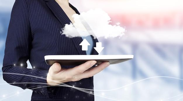 ソフトウェアコンピュータプログラムの更新ビジネス技術の概念をアップグレードします。デジタルホログラムクラウド、ダウンロード、明るいぼやけた背景にデータサイン付きの白いタブレットを手に持ってください。