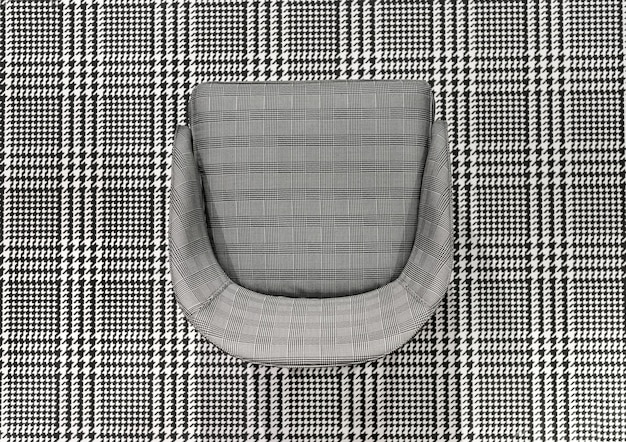 Upholstered checked pattern chair juxtaposed on matching black and white woven plaid textile in a top down view for high contrast effect for design