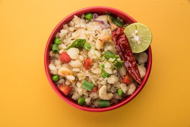Упма или уппитту - популярное блюдо для завтрака в южной индии и махараштре. основные ингредиенты - манная крупа, рава или рисовая мука грубого помола. подается в миске на красочном или деревянном фоне.