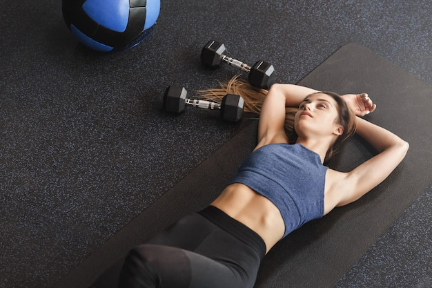 Upper angle dreamy young sportswoman lying on rubber mat at gym floor.