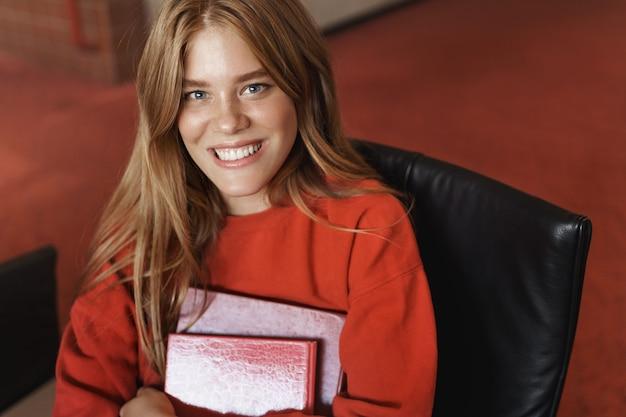 スマートな笑顔の赤毛の女の子の上部の角度のビューは、図書館に座って勉強し、晴れやかな笑顔で本を持っています。