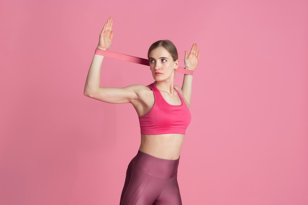 Upper body. beautiful young female athlete practicing , monochrome pink portrait. sportive fit caucasian model with elastics. body building, healthy lifestyle, beauty and action concept.