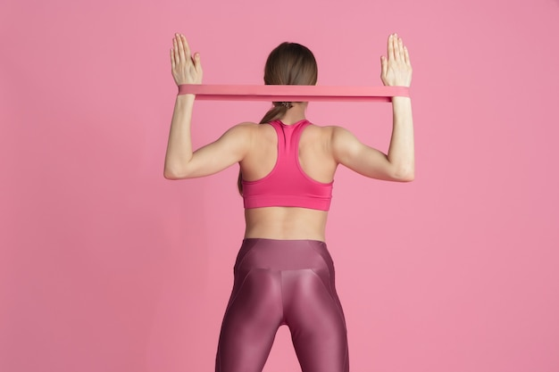 Upper body. beautiful young female athlete practicing in studio, monochrome pink portrait.