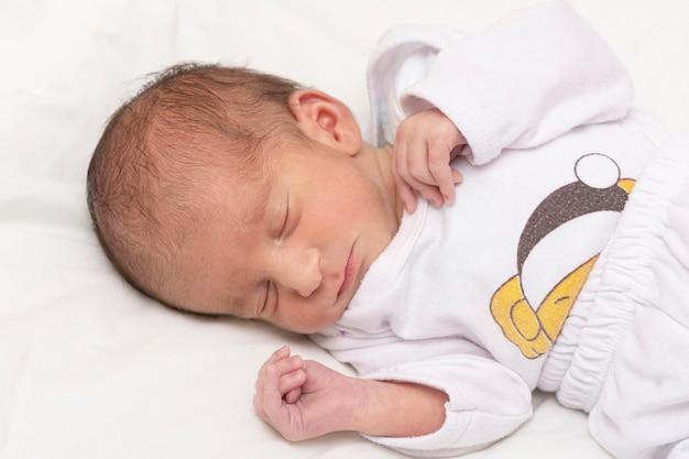 Портрет новорожденного ребенка, мирно спящего в постели