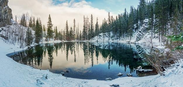 겨울철에 상부 그라시 호수. 거울처럼 호수 표면의 반사. 캐나다 앨버타 주 캔모어.