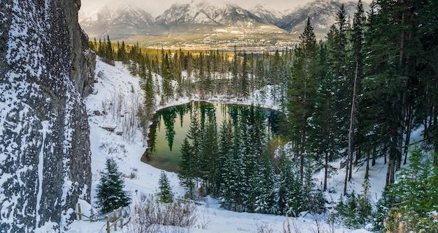 Озера верхнего грасси в зимний сезон. отражение поверхности озера как в зеркале. канмор, альберта, канада.