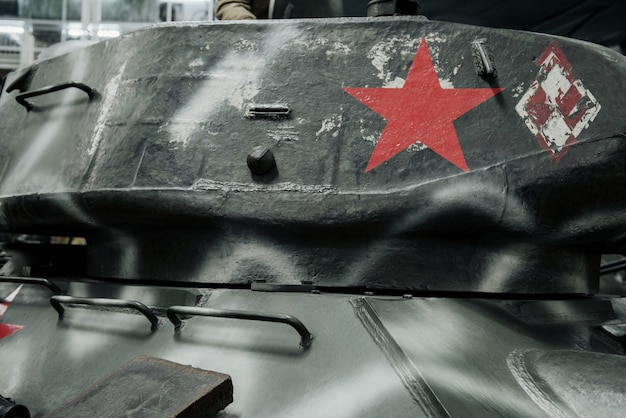 Upper part with red star on powerful old black tank at the exhibition