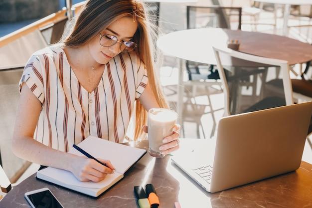 Верхнее фото симпатичной девушки, которая работает в тетради, сидит за компьютером с чашкой кофе.