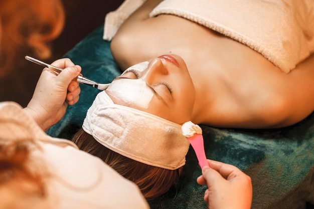 Upper view of a beautiful woman doing a while skin care mask on her face in a wellness spa center.