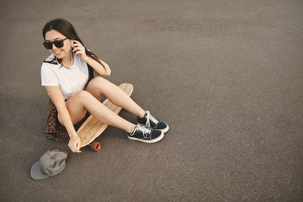 Upper view carefree hipster girl in sunglasses, snapback on the ground