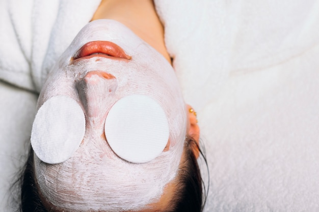 Upper view of a charming european female resting on a spa bed with a anti age white mask with white tissues on her eyes.