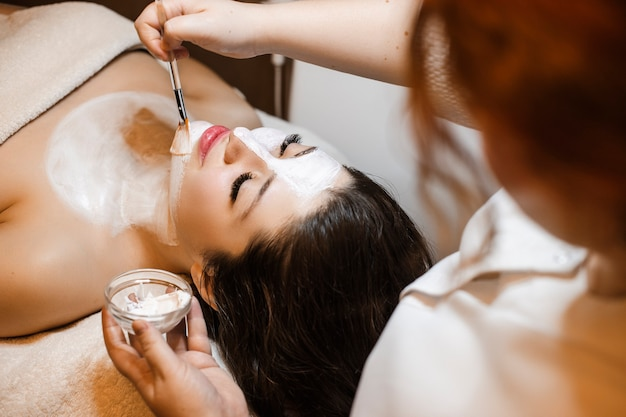 Upper view of a charming young female having facial procedures in a wellness spa center.