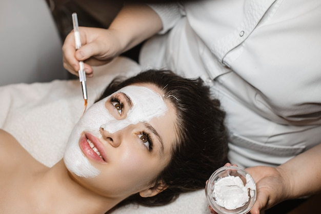 Upper view of a la young lovely woman having a hydration mask on her face while leaning on a spa bed .