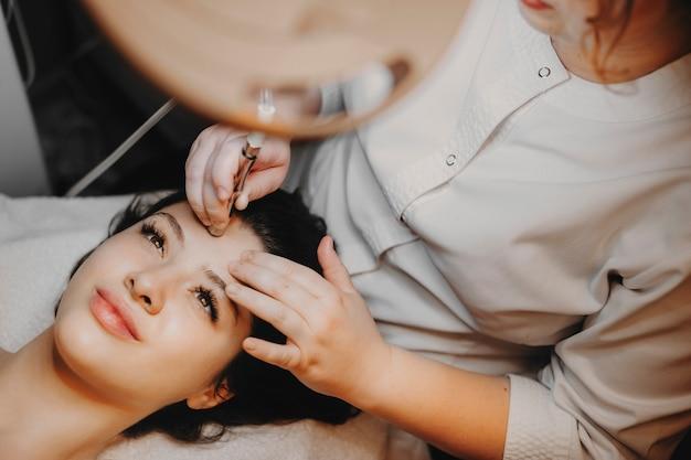 Вид сверху: красивое женское лицо, опирающееся на спа-кровать с открытыми глазами, которое делает неинвазивную микродермабразию на лице косметологом в спа-центре.