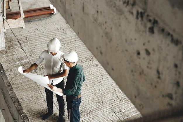 성인 arhitecht와 그의 작업자가 작업 현장에 건설중인 건물에 대해 이야기하는 상단보기.