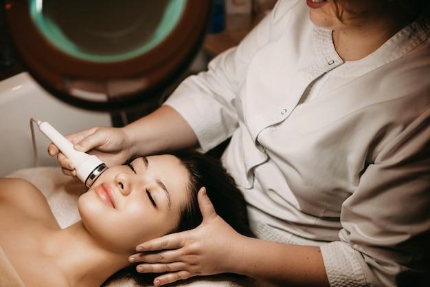 Вид сверху красивой женщины, имеющей процедуру электропорации на лице в спа-курорте.