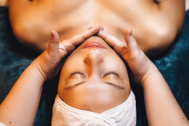 웰빙 스파 센터에서 알지네이트 마스크 후 웰빙 얼굴 절차를 갖는 동안 닫힌 눈으로 스파 침대에 기대어 아름다운 여성의 위보기