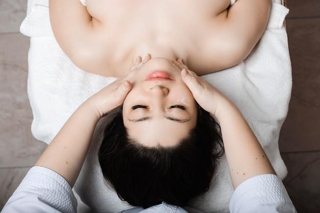 Вид сверху красивой молодой женщины, опирающейся на спа-кровать с закрытыми глазами, расслабляющей во время массажа лица косметологом в спа-центре.