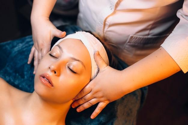 Вид сверху очаровательной женщины, занимающейся лицевой терапией на оздоровительном спа-курорте.