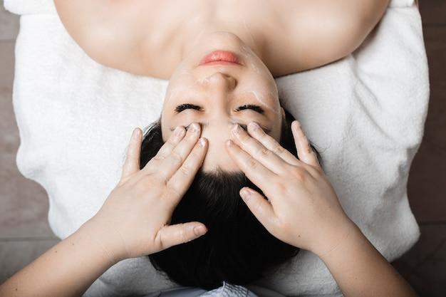 Вид сверху очаровательной молодой женщины, которая делает массаж лица, опираясь на спа-кровать в оздоровительном спа-центре.
