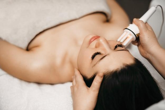 Вид сверху очаровательной молодой женщины, делающей мезотерапию на лице в салоне клиники, опираясь на кровать с закрытыми глазами.