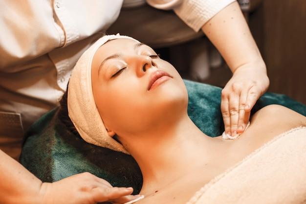 Вид сверху очаровательной молодой женщины, опирающейся на спа-кровать с закрытыми глазами и выполняющей процедуру очистки кожи.