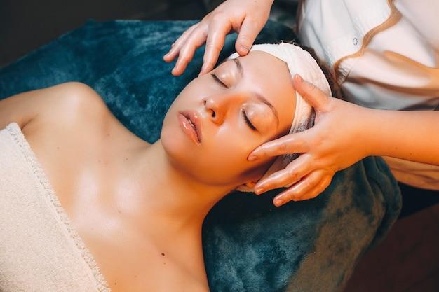 Вид сверху на симпатичную женщину, которая занимается косметологическим уходом за кожей с гиалуроновой кислотой на оздоровительном курорте.