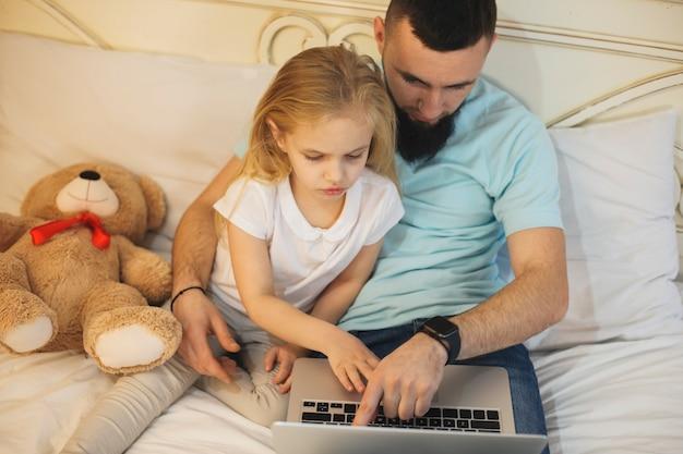 朝、自宅で父親がベッドに寄りかかってノートパソコンの画面を見ている素敵な小さな子供の上面図。映画を見ている父と娘。