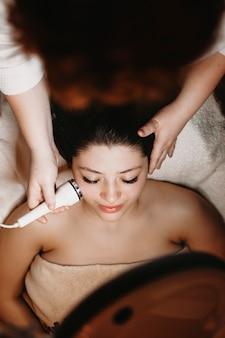 Вид сверху красивой женщины, проходящей терапию электропорации в оздоровительном спа-центре косметологом.