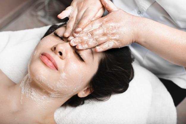 죽은 피부를 제거하기 위해 거품으로 얼굴 마사지를하는 닫힌 눈을 가진 스파 침대에 기대어 사랑스러운 젊은 백인 여성의 위보기.